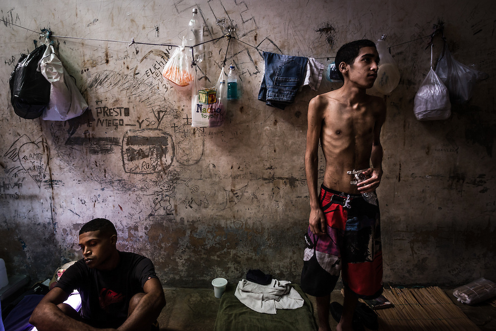 GUARENAS, VENEZUELA - NOVEMBER 14, 2016: Men pass the time resting in a jail cell in the outskirts of Caracas.  The majority in this cell were arrested for stealing, and had held regular jobs their entire lives, but turned to crime once the economic crisis sharply devalued their salaries, and they could not afford to support their families anymore.  Conditions in Venezuelan jails are inhumane. Those detained have to rely on family members to bring them food and water and personal items, but most come from working class families that are struggling to eat because of the economic crisis and skyrocketing food prices in Venezulea - that most cannot spare food to bring to their family members, or pay the bus fare to bring it to them.  The men said they are always hungry. They showed signs of being undernourished, and claimed to have lost dozens of pounds each since being detained.  The jails are overcrowded and the justice system is over capacity for processing cases, causing men in local jails to wait several months, and some several years, before having their case processed.  PHOTO: Meridith Kohut for The New York Times