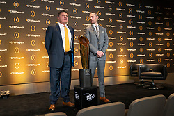 LSU head coach Ed Orgeron and Oklahoma head coach Lincoln Riley post for a photo with the CFP Championship trophy during a news conference ahead for the College Football playoffs, Thursday, Dec. 12, 2019, in Atlanta. Oklahoma will face LSU in the Chick-fil-A Peach Bowl. (Paul Abell via Abell Images for the Chick-fil-A Peach Bowl)