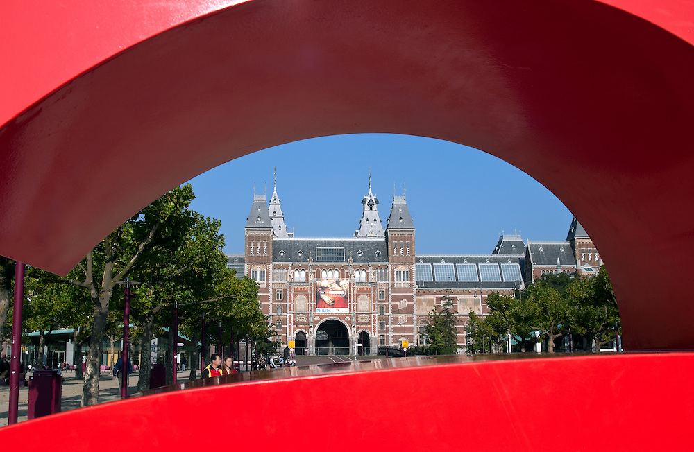 "The front of the Rikjsmuseum is framed by a portion of the ""I Amsterdam"" sculpture in the adjacent park."