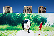 An advertisement features a smiling woman with a small shovel at a luxury housing development in Dong Li lake near Tianjin.