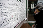 A woman looks through a list of the names of people who have been delivered to a temporary morgue inside the Ishinomaki Municiple Gymnasium in Ishinomaki, Japan on 15 March, 2011.  Photographer: Robert Gilhooly