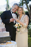 Middle-aged couple toasting near wedding cake, portrait
