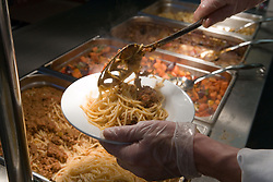 Kitchen assistant serving out spaghetti onto dinner plate during lunchtime,