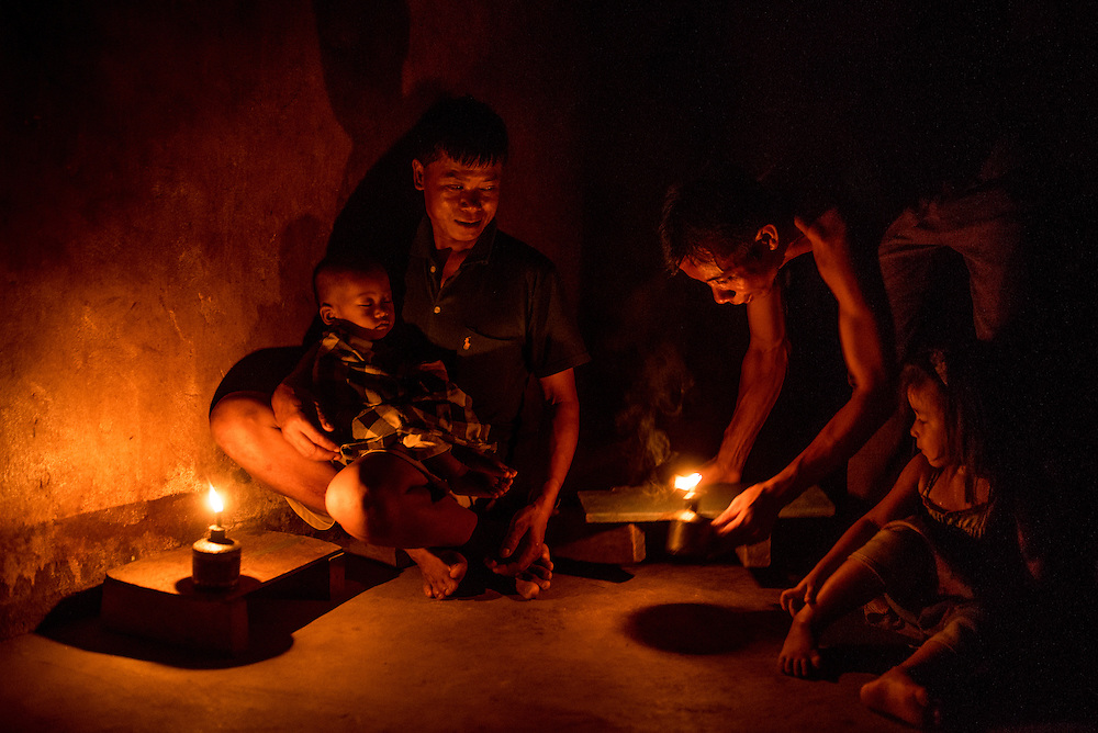 A family who cannot afford a water turbine  uses oil lamps to light their home in Khoc Kham, Laos. The village is not connected to the main electrical grid and many residents operate their own turbines to power lights and sometimes small appliances.