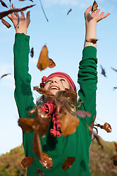 Close up of a smiling young girl with her arms stretched throwing leaves in the air