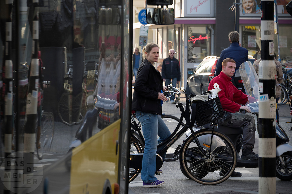 In Utrecht wacht een vrouw met de fiets en een jongen op een scooter tot ze kunnen oversteken terwijl er een bus aankomt.<br /> <br /> In Utrecht a woman on a bike and a boy on a scooter are waiting to cross while a bus is arriving.