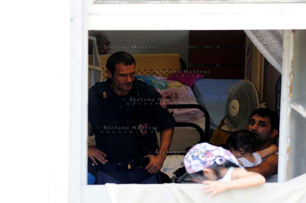 Roma 1 Settembre 2009.Sgomberato dalle Forze dell'Ordine  ex Ospedale Regina Elena, in via Castro Laurentiano,occupato da  due anni da 200 famiglie di senza casa..Agente di Polizia parla con una famiglia per farla uscire di casa...Rome, September 1, 2009.Vacated  by the police ex Ospedale Regina Elena, in via Castro Laurentiano, occupied by two years from 200 families homeless