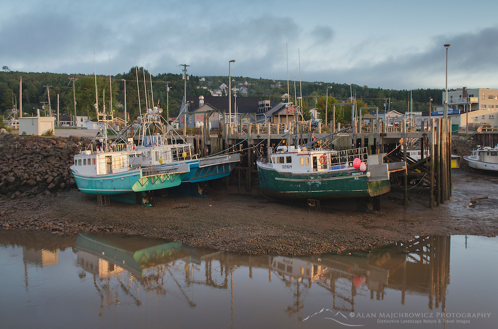 Fishing boats resting on mud bottom of Bay of Fundy during low tide, Alma New Brunswick