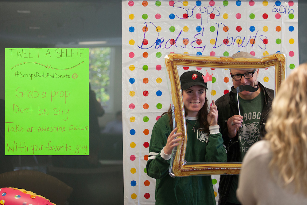"""Halle Weber and Tony Weber pose for a photo with donuts in Schoonover Center during """"Dad's and Donuts"""" on November 5, 2016."""