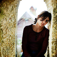 A young girl sitting in an old stone window frame looking sad