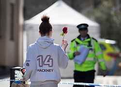 © Licensed to London News Pictures. 05/04/2018. London, UK. A girl wearing a top with the name of Hackney on it brings a single red rose to where a police tent covers the murder scene in Hackney after a 20 year old man was stabbed in Link Street. Police were approached by a man suffering from stab injuries at 8pm last night he was pronounced dead at 8. 24pm by officers. Photo credit: Peter Macdiarmid/LNP