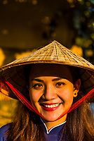 Beautiful Vietnamese woman wearing a Non la (conical palm leaf hat), Hoi An, Vietnam.