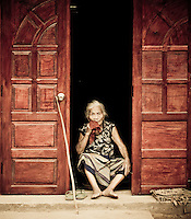 An elderly lady wipes her mouth with a red handkerchief on her front porch in the northern village of Muang Ngoi, Laos, Southeast Asia.