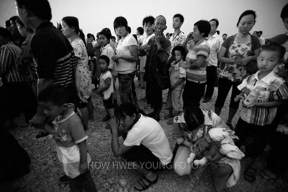 Migrant villagers of Cangfang town gather to board buses for relocation to neigbouring Hui county, more than 500 kilometers away, to make way for the colossal South-to-North Water Transfer project in Xichuan county of Henan Province in China on 29 June 2010. The South-to-North Water Transfer project, the largest known water diversion project, was conceived in 1952 to solve the country's chronic water shortages and involves creating three routes to channel 44.8 billion cu m of water from southern China to the northern areas. As part of the project's central route, affecting Henan and Hubei provinces, water from the Danjiangkou reservoir will be diverted to Beijing. The central route, which will raise the height of the Danjiangkou reservoir dam from 162 meters to 176.6 meters, requires the relocation of 330,000 people in Henan and Hubei provinces. Parts of Xichuan county, a remote, mountainous region inaccessible by railway and home to 162,000 migrants, the most anywhere, will be completely submerged by water from the Danjiangkou reservoir by 2014. The vast resettlement of affected residents in Xichuan county began in August 2009 and lasted till 2011.