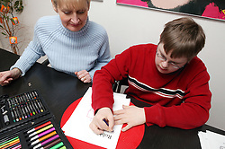 Single parent watching her son write his name on a piece of paper,