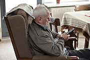 elderly man in armchair with remote control watching television