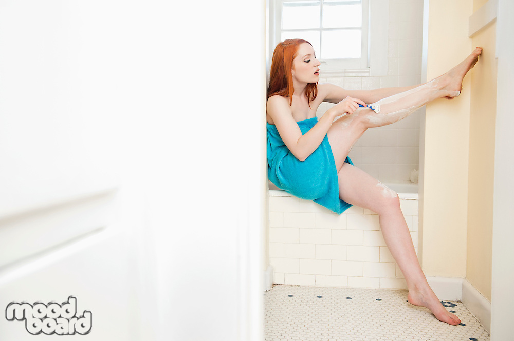 Young female shaving her legs on the side of the bathtub
