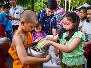 13 APRIL 2018 - BANGKOK, THAILAND:  Buddhist novices collect alms during a religious observance of Songkran in Lumpini Park in Bangkok. Songkran is the traditional Thai New Year celebration best known for water fights.    PHOTO BY JACK KURTZ