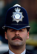 A close-up detail of a London Metropolitan police officer's face and helmet. Wearing a moustache and the famous tall helmet with the crest of the Met Police on the front.