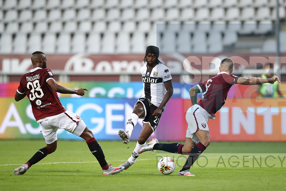 Parma Calcio's Ivorian striker Gervinho shoots gowlards past Torino FC's Cameroonian defender Nicolas Nkoulou and Italian defender Armando Izzo during the Serie A match at Stadio Grande Torino, Turin. Picture date: 20th June 2020. Picture credit should read: Jonathan Moscrop/Sportimage