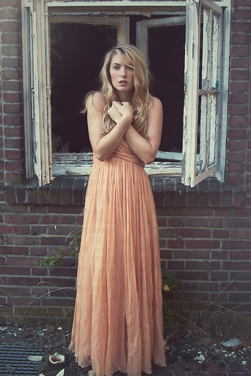 Young adult female with long blonde hair looking at camera standing beside window