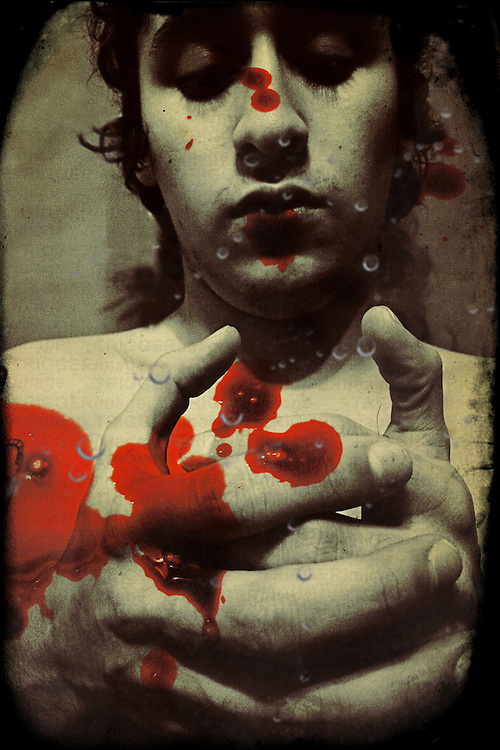 A young adult looking into hands with blood stains