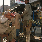 People drink water next to a food stall in varanasi. Drinking water is an art in India as people drink without touching their lips to the glass.