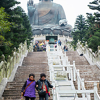 Two women descend the stairway under the watchful 112-foot tall Tian Tan Buddha on Lantau Island in Hong Kong.