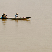 Two men in a sampan, a small, narrow boat, wearing conical hats on the Perfume River in Hue in central Vietnam.