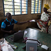Data clerk Oscar Kai hands a mother her child's medical record book at an outreach clinic at the Ngamani Primary School . Moms bring their children for routine check-ups and vaccinations and Oscar enters patient information into his computer about the PCV 10 vaccine, as well as pentavalent, BCG, polio, yellow fever, measles, diphtheria, tetanus and hepatitis B immunizations. All of that information is then uploaded to portable hard-drives that are returned weekly to the study headquarters, where the database is updated.<br /> <br /> &quot;Because the database is digitized, it means it's far easier to keep our records fresh, even if children move and access health services in different locations,&quot; says Dr. Benjamin Tsofa, the Kenyan health ministry's chief liaison on the study. <br /> <br /> In January 2011, the Kenyan government with support from the GAVI Alliance, introduced a new vaccine, PCV-10, which targets 10 bacteria than can cause Invasive Pneumococcal Disease.The vaccine's impact is monitored through an electronic database, part of the GAVI funded PCV impact study, which maps the growing coverage of the new vaccine. Already, here in Kilifi, the incidence of the illness in children aged five has gone down by approximately two-thirds.