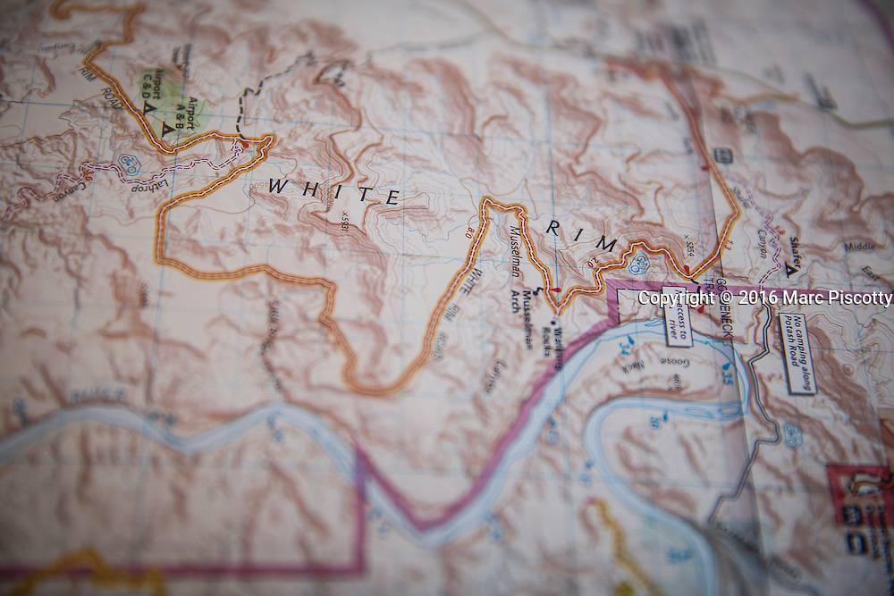SHOT 10/14/16 12:24:46 PM - A map detailing the White Rim trail. It is a mountain biking trip in Canyonlands National Park just outside of Moab, Utah. The White Rim Road is a 71.2-mile-long unpaved four-wheel drive road that traverses the top of the White Rim Sandstone formation below the Island in the Sky mesa of Canyonlands National Park in southern Utah in the United States. The road was constructed in the 1950s by the Atomic Energy Commission to provide access for individual prospectors intent on mining uranium deposits for use in nuclear weapons production during the Cold War. Four-wheel drive vehicles and mountain bikes are the most common modes of transport though horseback riding and hiking are also permitted.<br /> (Photo by Marc Piscotty / &copy; 2016)