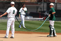 14 April 2013:  Members of the IWU Titans work to prepare the field for play including watering down the dirt infield during an NCAA division 3 College Conference of Illinois and Wisconsin (CCIW) Baseball game between the Elmhurst Bluejays and the Illinois Wesleyan Titans in Jack Horenberger Stadium, Bloomington IL