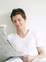 Young man reading newspaper in bed and smiling