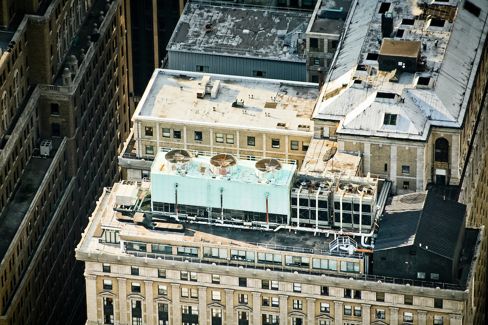 Air Conditioning units on top of an NYC building. Rich detail and texture of the old roofs.
