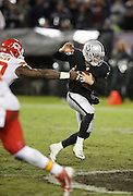 Oakland Raiders quarterback Derek Carr (4) gets sacked by Kansas City Chiefs outside linebacker Justin Houston (50) in the fourth quarter during the NFL week 12 regular season football game against the Kansas City Chiefs on Thursday, Nov. 20, 2014 in Oakland, Calif. The Raiders won their first game of the season 24-20. ©Paul Anthony Spinelli