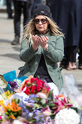 © Licensed to London News Pictures. 05/06/2017. London, UK. A woman prays as she lays flowers at London Bridge for those that lost their lives in the terrorist attack that took place on Saturday 3 June 2017. Three attackers drove a van at pedestrians before stabbing a number of people in nearby bars. Photo credit: Rob Pinney/LNP