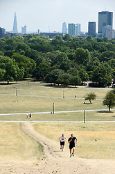 © Licensed to London News Pictures. 25/07/2018. LONDON, UK.  Men exercise on Primrose Hill amidst parched grass and hot conditions.  The forecast is for temperatures to rise to 35C by the end of the week.  Photo credit: Stephen Chung/LNP