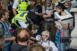 A Metropolitan Police officer seizes a megaphone being used by activists from HS2 Rebellion to tell a children's story during a protest rally in Parliament Square on 4 September 2020 in London, United Kingdom. The rally, and a later protest action at the Department of Transport during which activists glued themselves to the doors and pavement outside and sprayed fake blood around the entrance, coincided with an announcement by HS2 Ltd that construction of the controversial £106bn high-speed rail link will now commence.