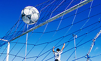 Soccer player walking away with arms up in victory as ball hits the back of the goal net