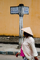 A woman wearing a traditional conical hat walks along the street in Hoi An Vietnam.