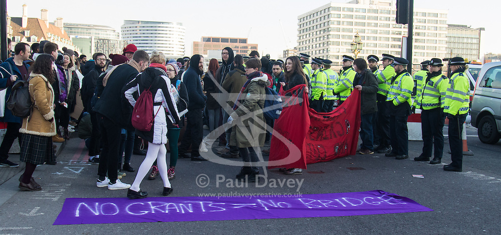 "Westminster, London, January 19th 2016. Students hold an ""emergency protest"" in Parliament Square and later blocking Westminster Bridge, against the cutting of maintenance grants. ""It took just 18 MPs 90 minutes to scrap maintenance grants for the million poorest students, without a debate in Parliament in a backroom committee"" PICTURED: Protesters block Westminster Bridge. ///FOR LICENCING CONTACT: paul@pauldaveycreative.co.uk TEL:+44 (0) 7966 016 296 or +44 (0) 20 8969 6875. ©2015 Paul R Davey. All rights reserved."