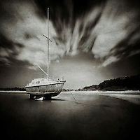 long exposure image of a yacht moored at low tide