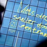 """Nederland Rotterdam 12 januari 2009 20090112 Foto: David Rozing ..Passanten wandelen langs Reusachtige spreuk Erasmus """" Niets droogte sneller dan een traan """" op gevel Zadkinecollege Hofplein. .Erasmus op stenen en tegels.Rotterdam, de geboortestad van Desiderius Erasmus, eert in 2008 één van de grootste denkers van zijn tijd. En dat zal de stad weten ook, met het project ' Erasmus op Straat '..Op tientallen gebouwen en winkelruiten en honderd stoeptegels komen van de vijftiende eeuwse wijsgeer. ..Desiderius Erasmus (1466-1536) is één van de grootste Nederlanders aller tijden...Foto: David Rozing"""