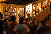 People line up while they wait to enter Gloria's elevator. There are several elevators in the old neighborhoods of Lisbon, which help people to go through the steep slopes of the city's hills. They constitute also a touristic attraction.