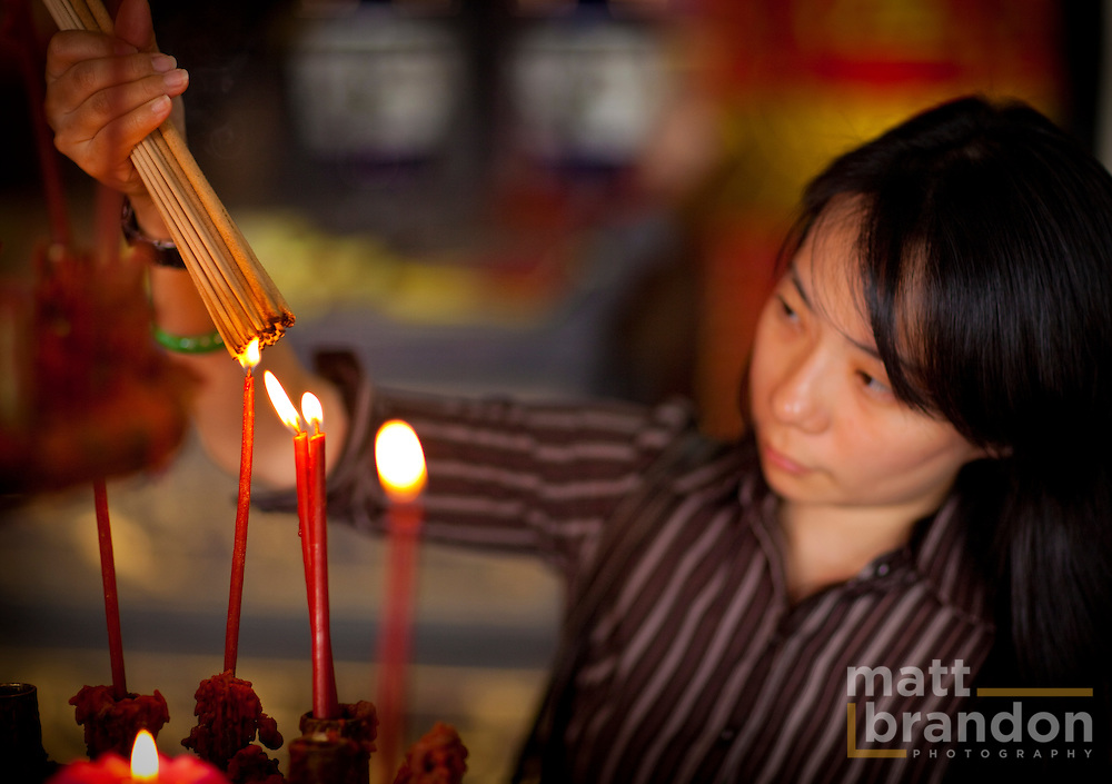 A woman lights incense in a Chinese temple to be used during her prayers.