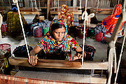 Ayshah Begum works on her rug at the Mornia Kik Rug Factory in Doani Villlage, Haragach Upazila, Rangpur, Bangladesh on 19th September 2011 where she works alongside 25 rural village women making rugs for German textile discounter Kik. Over 400 women have been economically empowered through the CARE Bangladesh WONDER Project that was completed recently. The WONDER Project's goals were to create sustainable income and employment opportunities for extremely poor women by training them in rug production for export. The women now earn about 4000 Bangladeshi Taka per month. The WONDER Project has now moved into a new phase that focusses on general healthcare, workplace safety and nutritional training and awareness programs. Photo by Suzanne Lee for The Guardian