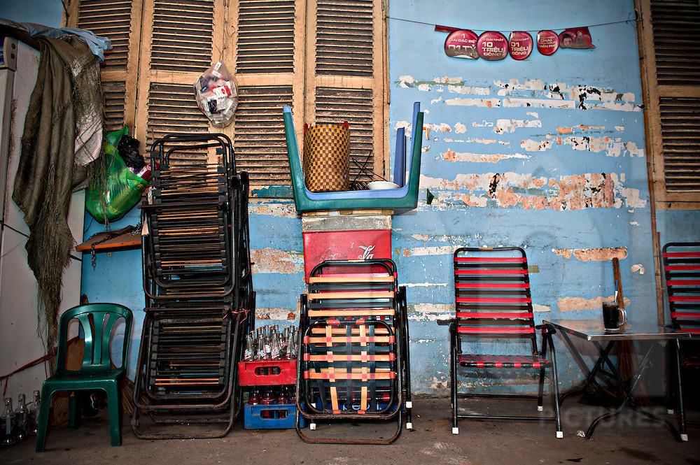 Chairs are piled up in front of a wall in District 1. Ho Chi Minh city, Vietnam, Asia