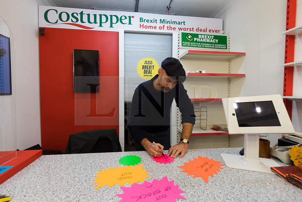 © Licensed to London News Pictures. 23/11/2018. London, UK.  A staff member writes 'out of stock' signs inside the People's Vote campaign stunt pop-up shop in Peckham High Street on Black Friday to show that the government's Brexit deal is a bad deal and the shop is stocked with household products, such as 'chlorinated' chicken to illustrate the bad deal. Photo credit: Vickie Flores/LNP
