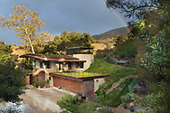 The Platinum level LEED Certified eco-friendly house showing integration into the hillside, green roof and solar roof panels.<br /> Rainbow in the sky above after a rain shower<br /> <br /> <br /> Coyote Residence, Montecito, CA<br /> Design: Susan Van Atta and Ken Radtkey