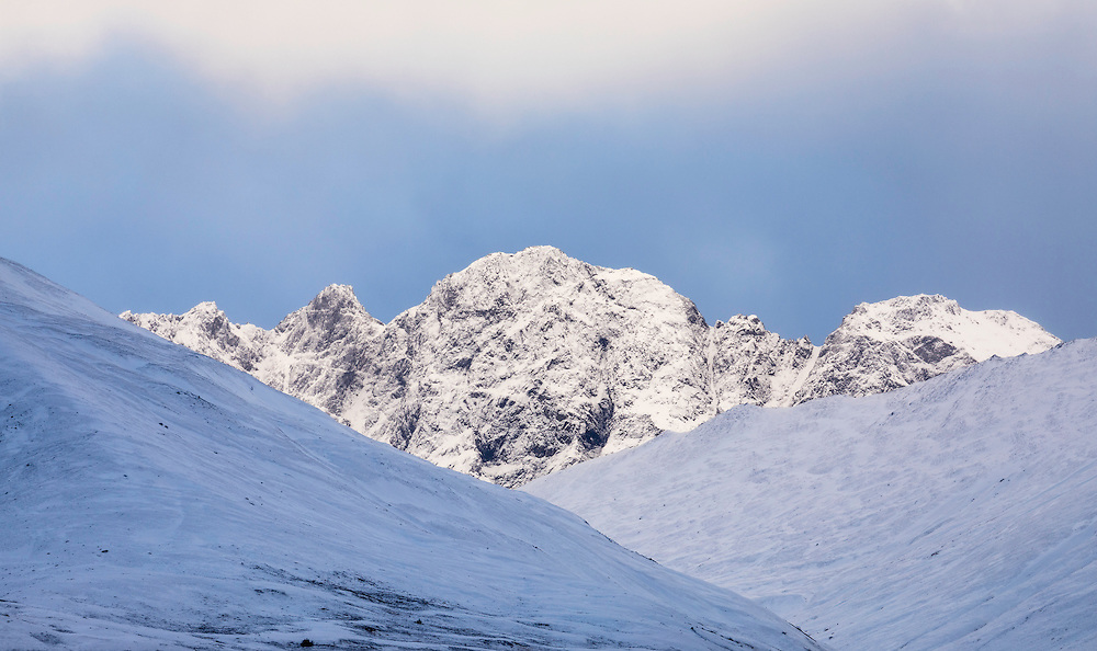 Parting clouds illuminate a peak in the Chugach Mountains near Eagle River in Southcentral Alaska. Winter. Afternoon.